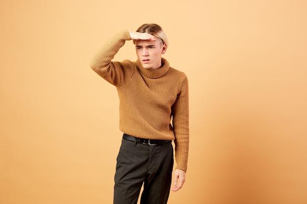 Giovane ragazzo biondo vestito con maglione color senape e pantaloni neri è in posa con la mano sulla fronte in studio sullo sfondo beige.