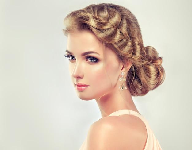Giovane donna dai capelli bionda con matrimonio elegante alla moda o acconciatura da sera con ampia treccia che circonda la sua testa e vivido trucco sul viso