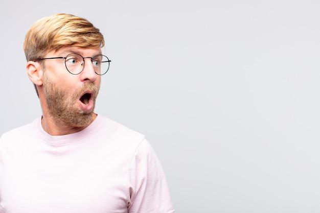 Giovane uomo biondo sorpreso o scioccato
