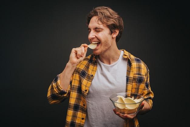 Il giovane uomo biondo in camicia gialla sta mangiando le patatine fritte e sta tenendo il piatto con esso