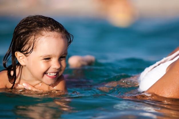 Giovane madre bionda in bikini blu in piedi in acqua e aiutando a nuotare la sua piccola figlia sorridente al sole il giorno d'estate. vacanze in famiglia e concetto di viaggio