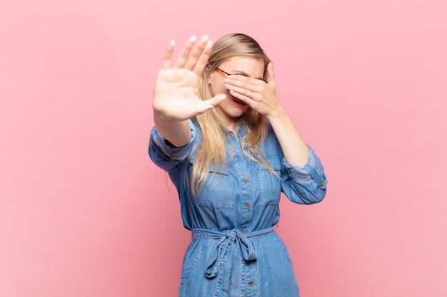 Giovane bella donna bionda che copre il viso con la mano e mette l'altra mano davanti per fermarsi, rifiutando foto o immagini