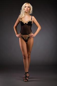 Giovane donna bionda sottile in lingerie nera sexy e scarpe col tacco alto in piedi
