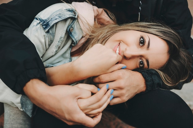 Giovane donna bionda tra le braccia del raccolto uomo seduto sui gradini e sorridere alla telecamera