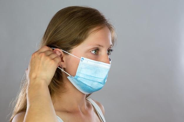Giovane donna bionda che attacca la mascherina chirurgica al suo fronte