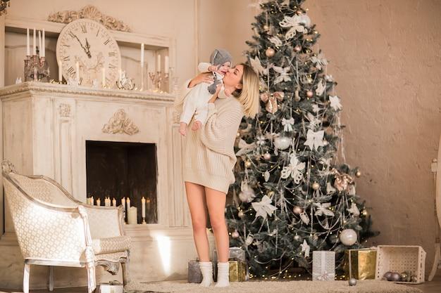 Giovane donna bionda in maglione lungo beige che abbraccia piccolo neonato nel vestito di natale