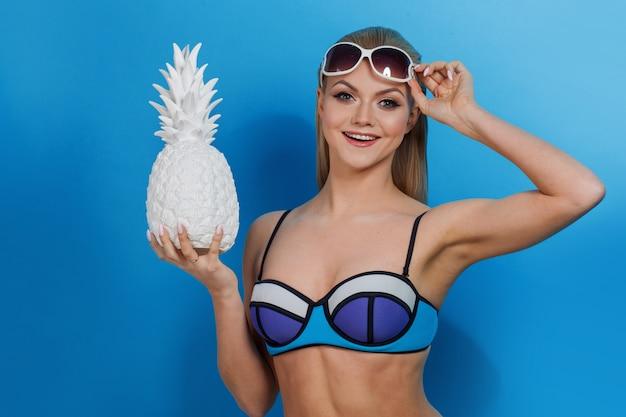 Giovane donna bionda in bikini blu su blu, con occhiali da sole e ananas bianco