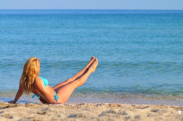 Giovane donna bionda in bikini blu che si siede sul bordo del mare con le gambe sollevate