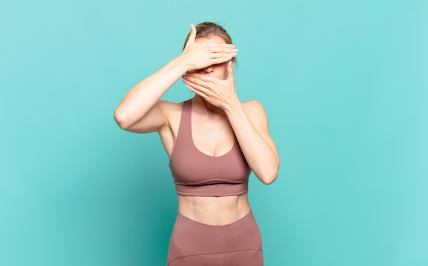 Giovane donna bionda che copre il viso con entrambe le mani dicendo no alla telecamera! rifiutare le foto o vietare le foto. concetto di sport