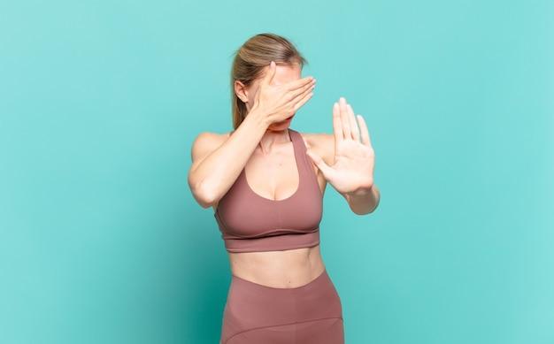 Giovane donna bionda che copre il viso con la mano e mette l'altra mano davanti per fermare la fotocamera, rifiutando foto o immagini. concetto di sport