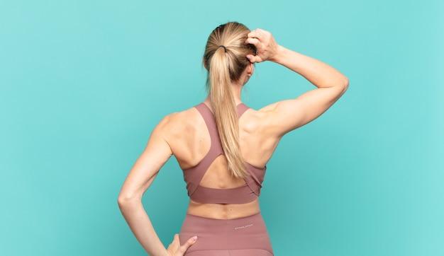 Giovane donna bionda che si sente all'oscuro e confusa, pensando a una soluzione, con la mano sull'anca e l'altra sulla testa, vista posteriore. concetto di sport
