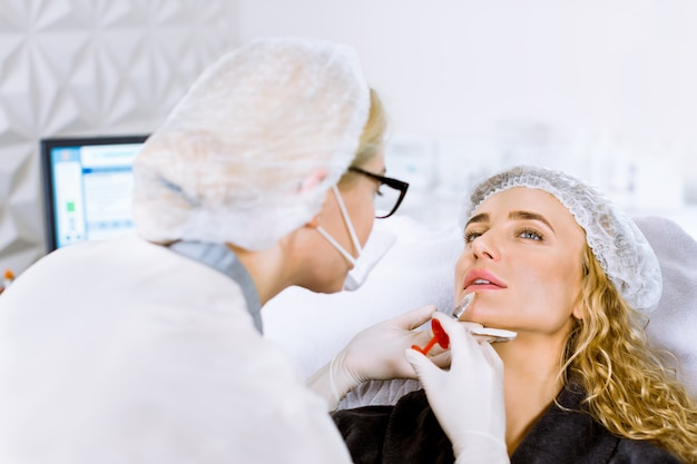 La giovane donna bionda ottiene un'iniezione nelle sue labbra nel salone di bellezza. iniezioni di bellezza - donna che giace nell'ufficio dell'estetista.