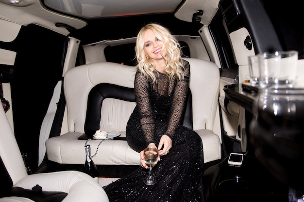 Giovane donna bionda che ha festa con champagne e torta in limousine