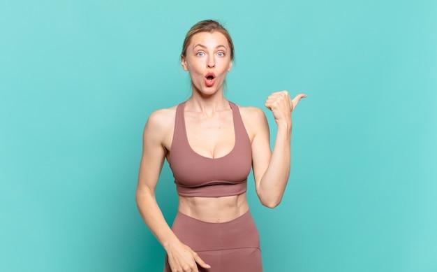 Giovane donna bionda che sembra stupita per l'incredulità, indicando un oggetto sul lato e dicendo wow, incredibile. concetto di sport