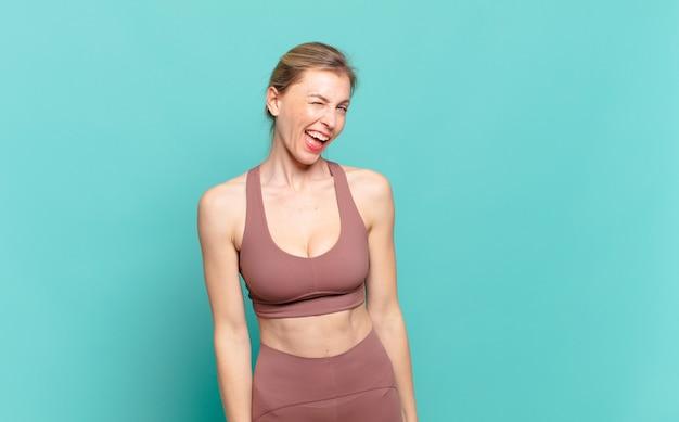 Giovane donna bionda che sembra felice e amichevole, sorride e ti fa l'occhiolino con un atteggiamento positivo. concetto di sport