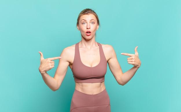 Giovane donna bionda che sembra orgogliosa, positiva e casual che indica il petto con entrambe le mani. concetto di sport