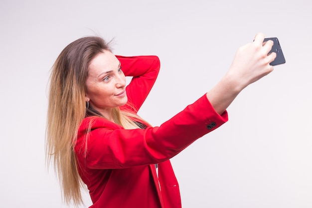 Giovane donna bionda che fa selfie in studio