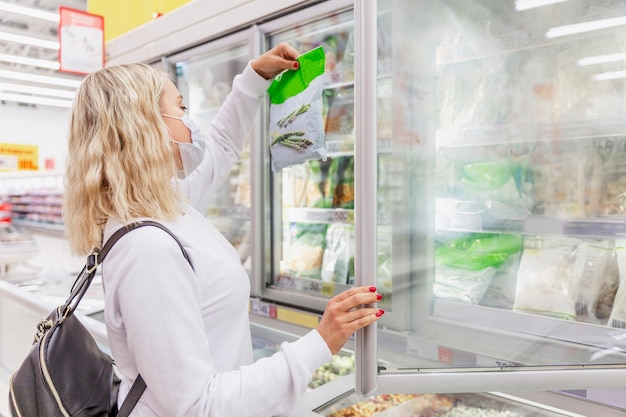 Giovane donna bionda in una maschera medica nel reparto alimenti congelati. salute e corretta alimentazione durante una pandemia.