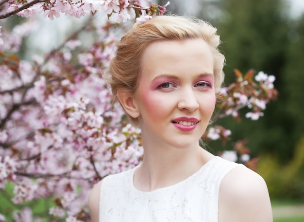 Giovane donna bionda su una rosa di fiori di ciliegio in primavera, da vicino