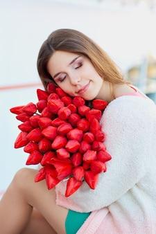 Giovane donna bionda che sorride con un mazzo di tulipani rossi Foto Premium