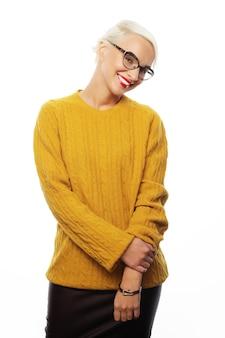 Giovane donna bionda che indossa un maglione giallo isolato su white