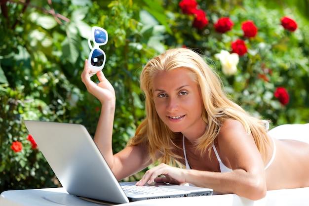 Giovane donna bionda in bikini bianco sdraiata sul lettino con il computer portatile su piante verdi