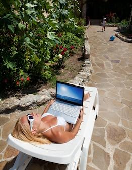 Giovane donna bionda in bikini bianco sdraiata sul lettino con laptop