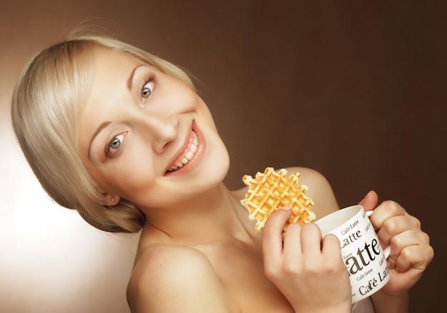 Giovane donna bionda con caffè e biscotti