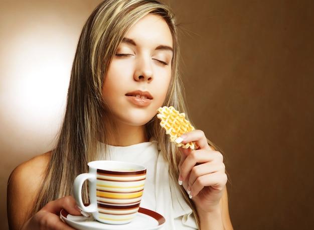 Giovane donna bionda con caffè e biscotti.
