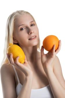 Giovane donna bionda con limone e arancia isolato su una superficie bianca