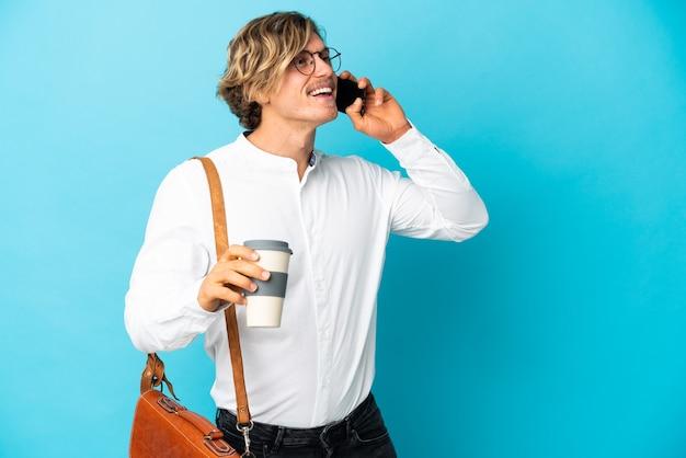 Giovane uomo d'affari biondo isolato sulla parete blu che tiene caffè da portare via e un cellulare