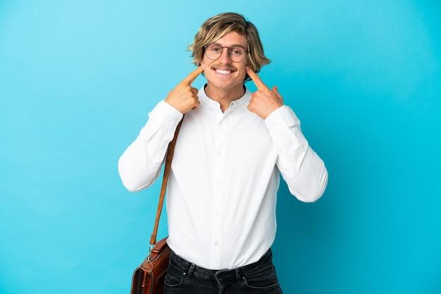 Giovane imprenditore biondo isolato sorridente con un'espressione felice e piacevole