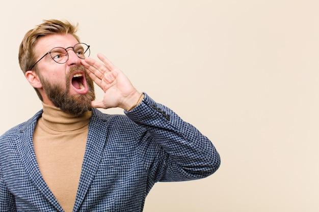 Giovane uomo d'affari biondo che urla ad alta voce e rabbiosamente per copiare lo spazio sul lato, con la mano accanto alla bocca