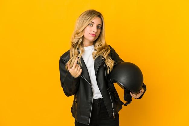 La giovane donna caucasica bionda del motociclista che tiene il casco che indica con il dito contro di voi come se invitando si avvicini.