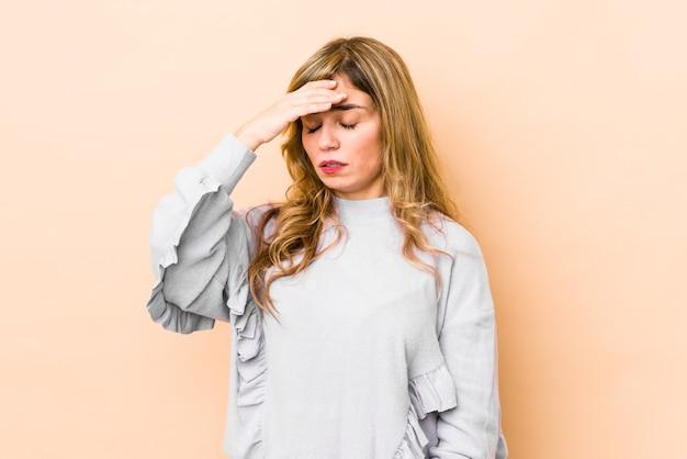 Giovane donna bionda caucasica con mal di testa, toccando la parte anteriore del viso.