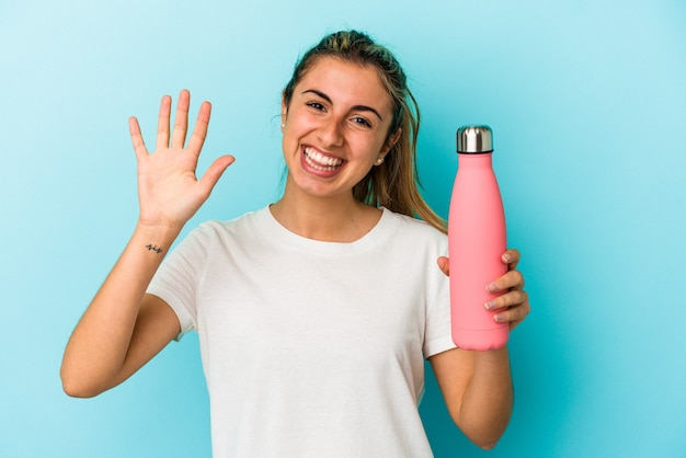 Giovane donna caucasica bionda che tiene un termo isolato su sfondo blu sorridente allegro che mostra il numero cinque con le dita.