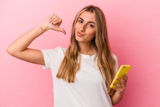 La giovane donna caucasica bionda che tiene un telefono mobile giallo isolato si sente orgogliosa e sicura di sé, esempio da seguire.