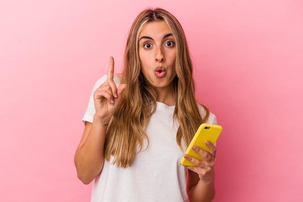 Giovane donna caucasica bionda che tiene un telefono cellulare giallo isolato avendo qualche grande idea, concetto di creatività.