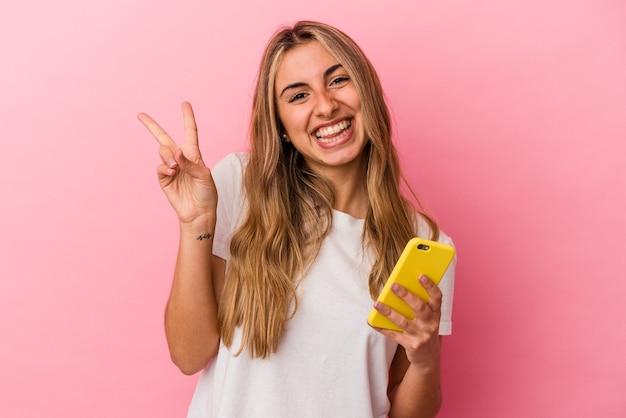La giovane donna caucasica bionda che tiene un telefono cellulare giallo ha isolato gioiosa e spensierata che mostra un simbolo di pace con le dita.