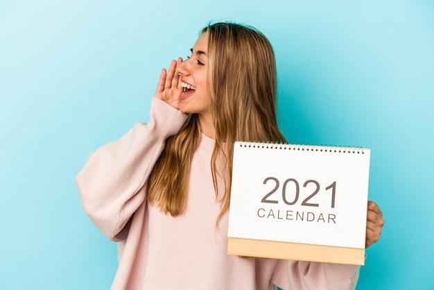 La giovane donna caucasica bionda che fora un calendario ha isolato gridando e tenendo il palmo vicino alla bocca aperta.