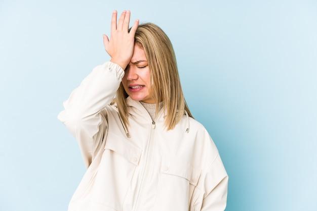 Giovane donna bionda caucasica isolata dimenticando qualcosa, schiaffi sulla fronte con il palmo e chiudendo gli occhi.