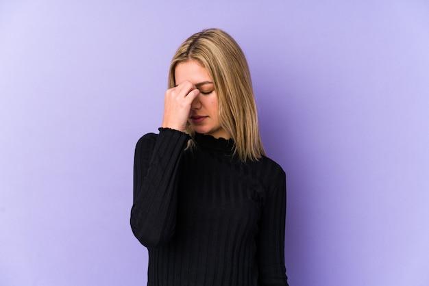 Giovane donna caucasica bionda isolata avendo un mal di testa, toccando la parte anteriore del viso.