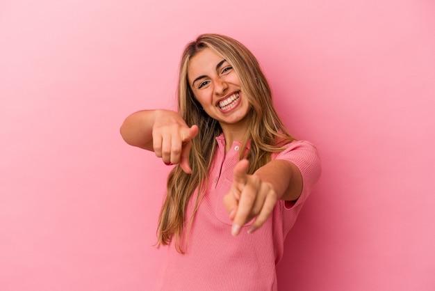 Giovane donna bionda caucasica isolata su sfondo rosa sorrisi allegri che punta alla parte anteriore.