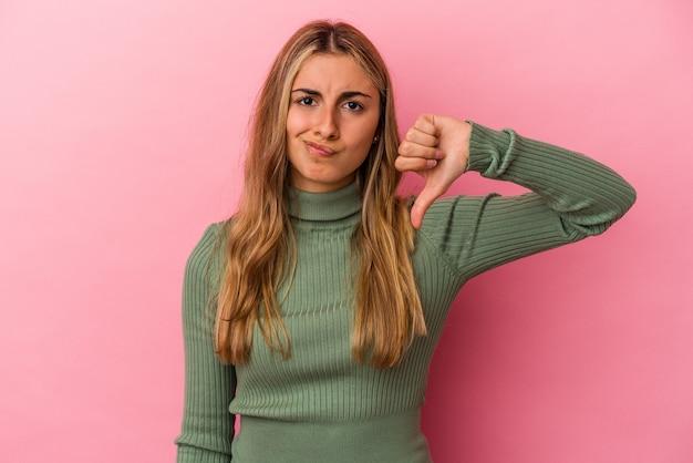 Giovane donna bionda caucasica isolata su sfondo rosa che mostra il pollice verso il basso, il concetto di delusione. Foto Premium