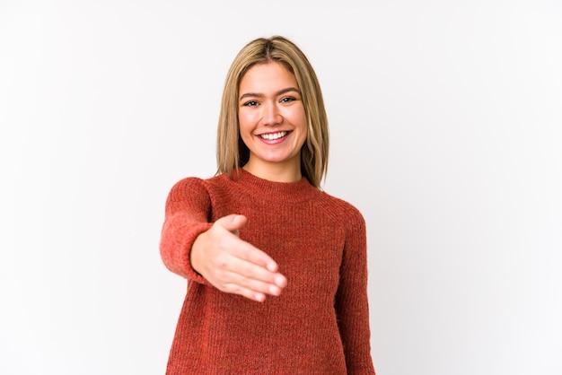 Giovane donna caucasica bionda isolata che allunga la mano alla macchina fotografica nel gesto di saluto.