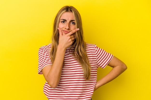Giovane donna bionda caucasica isolata su sfondo giallo contemplando, pianificando una strategia, pensando al modo in cui un business.