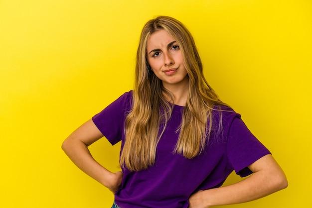 La giovane donna caucasica bionda isolata sul fronte accigliato della parete gialla nel dispiacere, tiene le braccia conserte