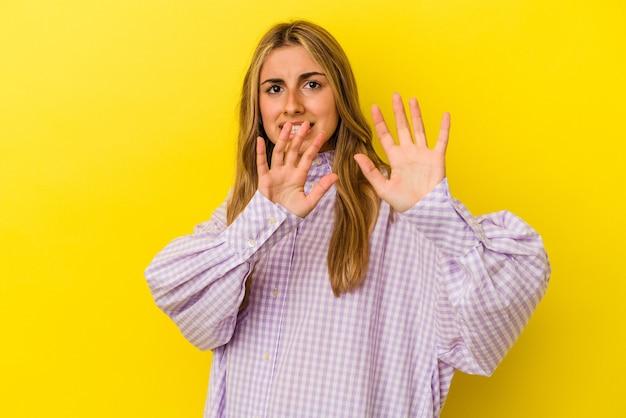Giovane donna caucasica bionda isolata sulla parete gialla che rifiuta qualcuno che mostra un gesto di disgusto