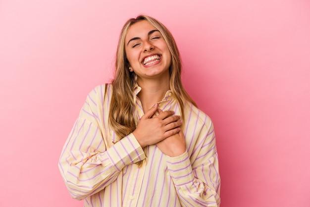 Giovane donna caucasica bionda che ride mantenendo le mani sul cuore, il concetto di felicità.