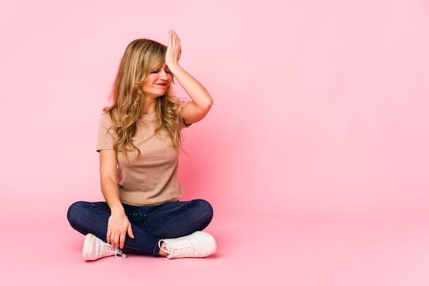 Giovane donna caucasica bionda seduta su uno studio rosa dimenticando qualcosa, schiaffi sulla fronte con il palmo e chiudendo gli occhi.